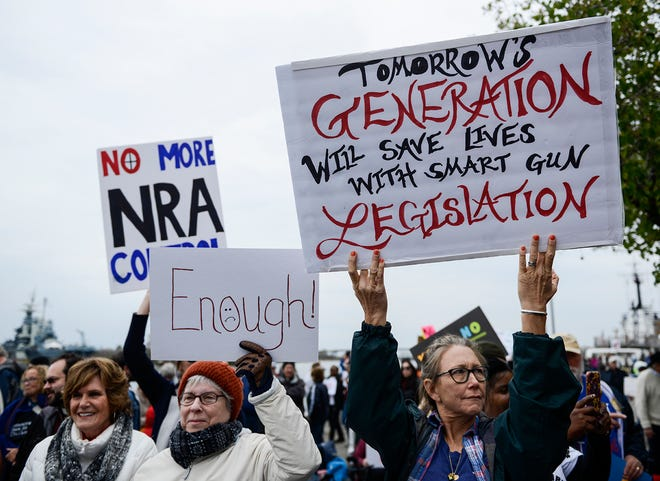Women hold signs at the March for Our Lives, gun reform peaceful protest in downtown Wilmington, N.C. on Saturday, March 24, 2018.