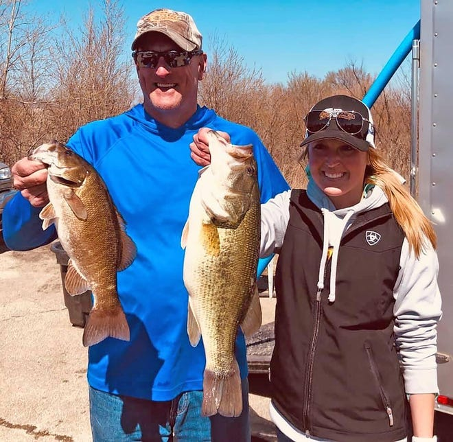 Abby Keeney, right, of Gardner, holds up one of her two big bass from the two-day Kansas BASS Nation 4-Man/Team Series tournament March 27-28 on Melvern Reservoir.