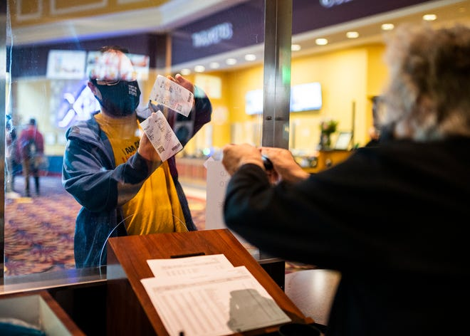 Dan Caci holds up his ticket to be scanned by Charlotte Gabree as moviegoers return to the theaters amid the COVID-19 pandemic to view Godzilla vs. Kong at Blackstone Valley 14 Cinema de Lux in Millbury on Wednesday, March 31, 2021.