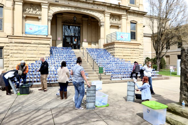 Volunteers place the pinwheels on the steps of the Tuscarawas County courthouse Wednesday in recognition of Child Abuse Prevention Month in April.