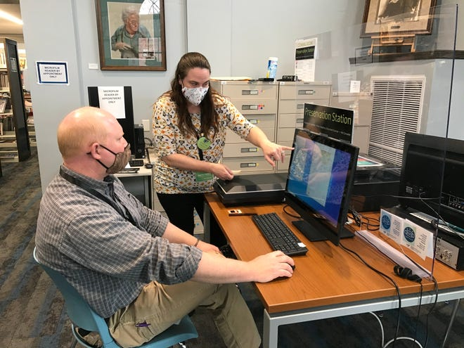 County Library Technology Training Coordinator Jessica Conley shows Assistant Director Brian Herzog how to use equipment in the Main Library's Preservation Station. Pictured, from left: Brian Herzog and Jessica Conley.