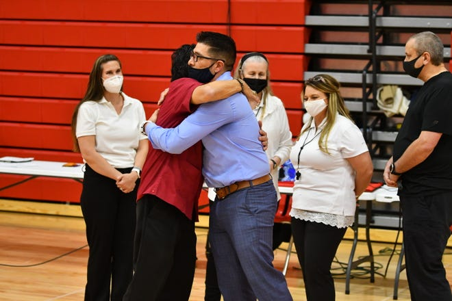 Pueblo Centennial coach Paul Arriaga, left, hugs son, Central coach Ramon Arriaga, right, before the two faced off for the first time Tuesday, March 30, 2021, at Centennial High School.