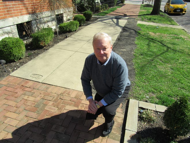 """Bill Curlis, a member of the German Village Society Board of Trustees, kneels on a sidewalk on Mohawk Street, displaying freshly repaired brick and cement. The GVS has termed 2021 as """"The Year of the Sidewalk,"""" with a renewed effort to get property owners to get their brick sidewalks fixed or convert concrete to brick."""