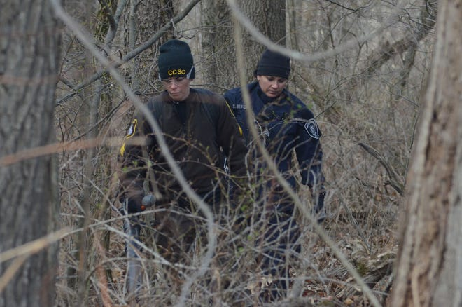 Officers search woods in Newton Township on Wednesday looking for the body of a Battle Creek woman missing since 2005.
