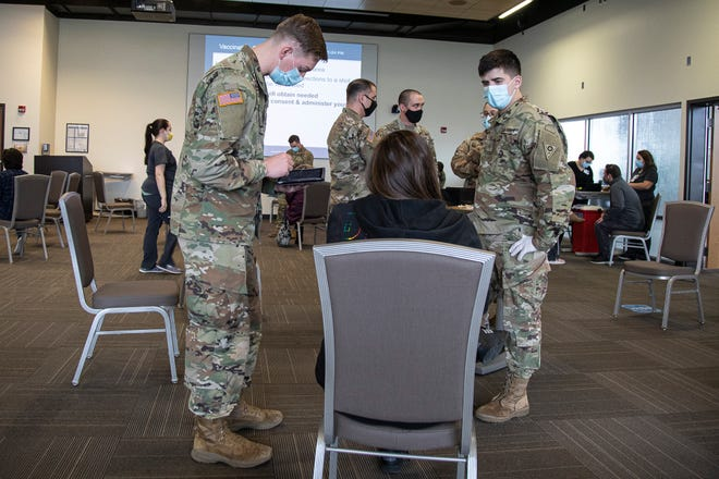 Joshua McLaughlin, left, takes a patient's information as Anthony Verduga, right, asks the patient which arm to give the vaccine recipient their shot in at Adena's PACCAR Center on March 31, 2021. Members of the Army National Guard came in to assist with the mass vaccination site.