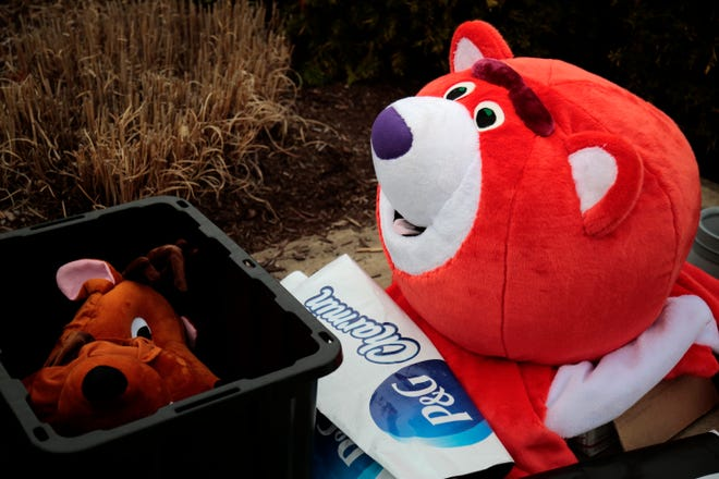 Mascot-style costumes of caribou and the Charmin brand bear are brought by protesters outside of the Kenwood Towne Center in Kenwood, Ohio, on Wednesday, March 31, 2021.