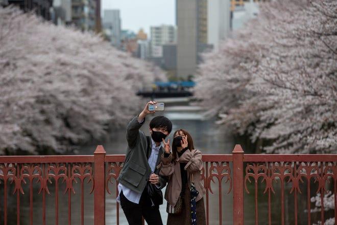 Orang-orang yang mengenakan masker pelindung untuk membantu mengekang penyebaran virus corona mengambil foto selfie di jembatan saat bunga sakura mekar di atas Sungai Meguro Minggu, 28 Maret 2021, di Tokyo.