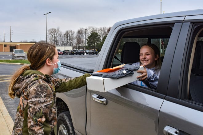 Layla Myers, left, volunteered to help distribute boxes during Vanguard's Spring Break in a Box pickup event. Myers is the niece of Vanguard Assistant Director Lyne Walby. Here, Myers hands a box to Megan Zgodzinski of Port Clinton.