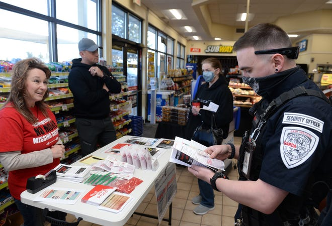 Shanna Bulik-Chism, left, president of the North Central Montana Human Trafficking and MMIP Task Force, hands out information and a packet of red sand to visitors to the Holiday Gas Station on Fox Farm Road Wednesday morning as part of the Red Sand Project. The project is raising awareness about the problem of human trafficking.