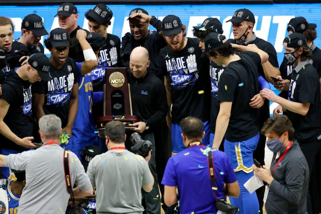 UCLA head coach Mick Cronin lifts the trophy after defeating Michigan during the Elite Eight round of the 2021 NCAA Tournament on Wednesday, March 31, 2021, at Lucas Oil Stadium in Indianapolis, Ind.