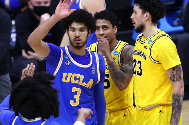 UCLA Bruins guard Johnny Juzang (3) high fives UCLA Bruins guard Tyger Campbell (10) after being fouled by Michigan during the Elite Eight round of the 2021 NCAA Tournament on Tuesday, March 30, 2021, at Lucas Oil Stadium in Indianapolis, Ind.