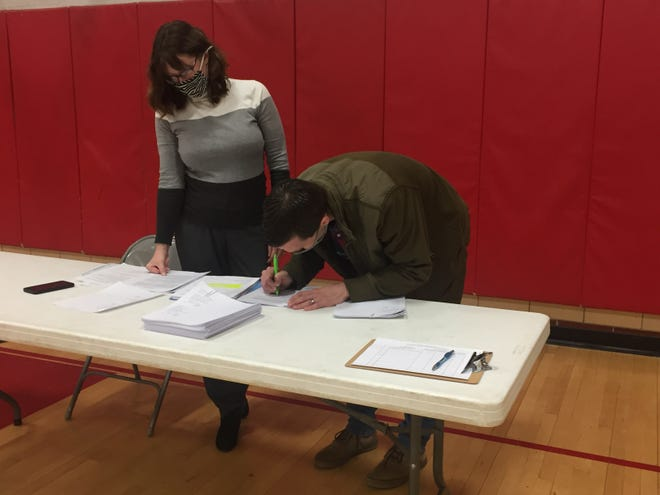 Ben Carver, lead pastor at Core Community Church, signs paperwork for Auburn and Dowds elementary schools after a public auction on Wednesday as Treasurer Beth Lykins looks on.