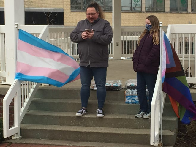 Kelli Quail, president of the Mansfield Gay Pride Association, reads a proclamation from President Joe Biden during a rally Wednesday in honor of Transgender Day of Visibility. Her daughter, Laura, looks on.