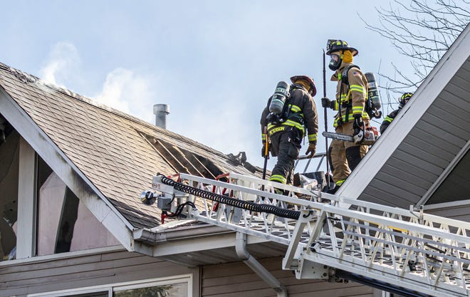 Firefighters work on the roof of a multi-family residential building at 224 Millington Lane in Hartland on Wednesday, March 31, 2021.