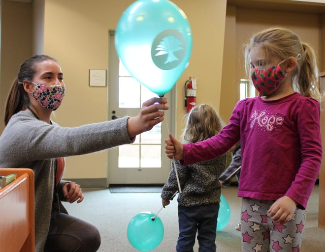 A young patron is greeted with a balloon as she enters the Library