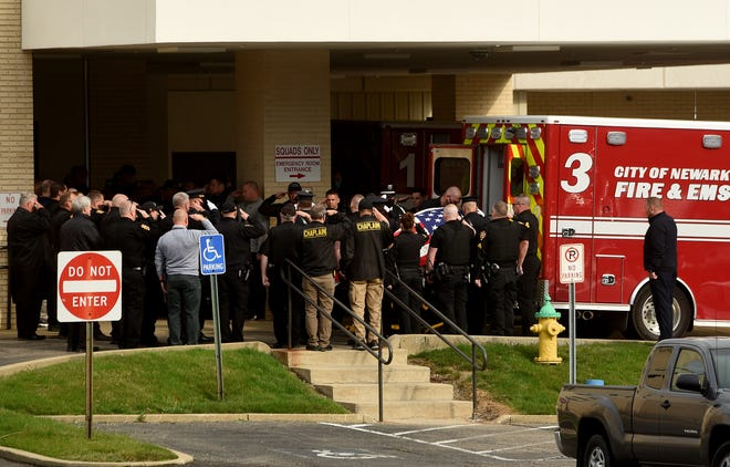 Local police, firefighters, and other city officials salute as  Newark Police Chief Steve Baum is taken from Licking Memorial Hospital to the Brucker & Kishler Funeral Home on Wednesday, March 31, 2021. Baum, 54, died suddenly from a health emergency Tuesday night.
