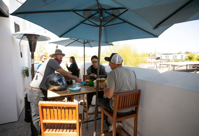 Paul Waxman, left, a co-owner of Belly, serves dishes tat the rooftop dining area at Belly, a restaurant at the intersection of Seventh Street and Camelback Road in Phoenix on March 31, 2021. Belly opened during the pandemic starting with takeout only and has phased into dine-in.
