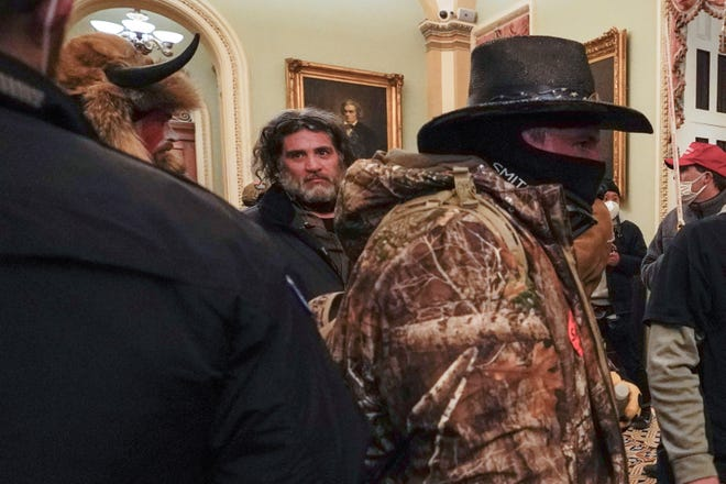 In this Jan. 6, 2021, file photo, rioters including Dominic Pezzola, center with beard, are confronted by U.S. Capitol Police officers outside the Senate Chamber inside the Capitol in Washington.