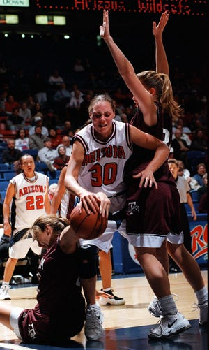 Arizona's Adia Barnes tries to drive between two Texas A&M players during the first half of the UA-Texas A&M women's basketball game at the McKale Center on Dec. 10, 1997.
