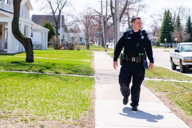 Port Huron Police Community Service Officer Duane Hunger walks through a Port Huron neighborhood Wednesday, March 31, 2021.