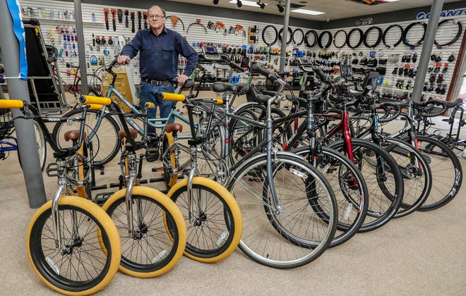 Harley Leikam, of Wolf Cycle and Fitness poses, Wednesday, March 31, 2021, with his remaining inventory of regular bicycles.