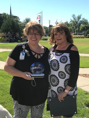 Lisa Brunk (left) holds the Sanford Health Egger Family Employee of the Year award along with Sabra Shields, who nominated her for the award.