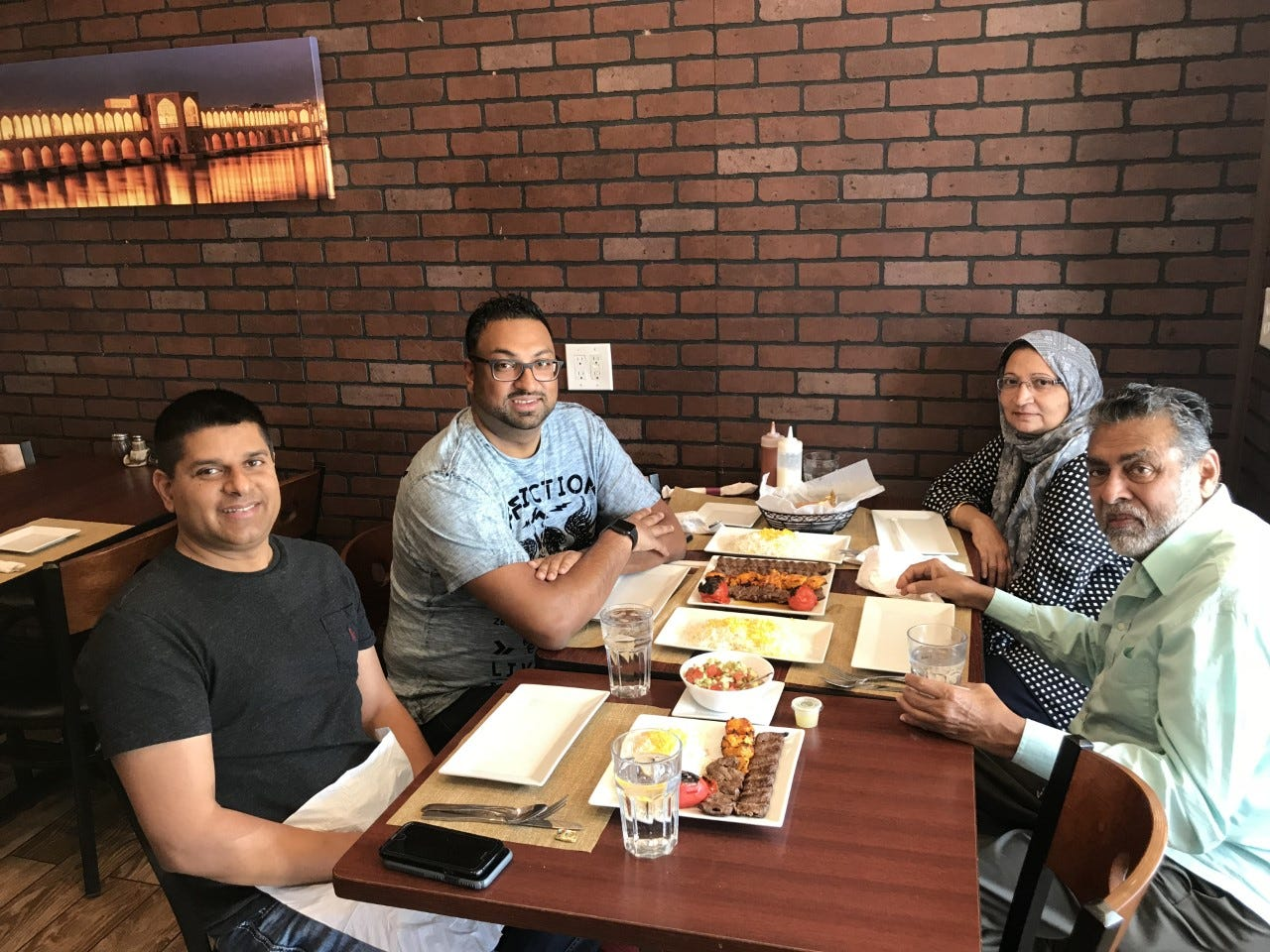 Sameer Sarmast sits with his cousin Sameer Ahmed and his parents, Amina and Syed Sarmast, at their favorite restaurant Kabob on the Cliff in Rutherford, New Jersey.