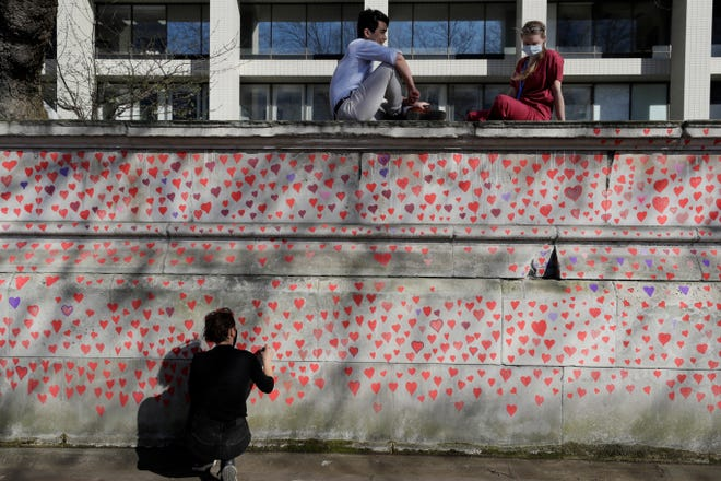 Hospital staff from St Thomas' Hospital watch from the top of the wall as members of bereaved families paint red hearts on the COVID-19 Memorial Wall opposite the Houses of Parliament on the Embankment in London, Monday March 29, 2021.