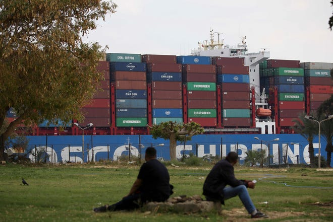 A cargo ship sails through the town of Ismailia, Egypt, Tuesday, March 30, 2021 as traffic resumed through the Suez canal after it was blocked by a massive ship that had been stuck sideways for nearly a week.