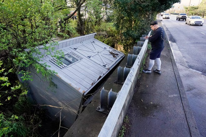 Adam Wirdzek stops to look at a utility building that was carried down a flooded creek Sunday, March 28, 2021, in Nashville, Tenn. Heavy rain across Tennessee flooded homes and roads as a line of severe storms crossed the state.