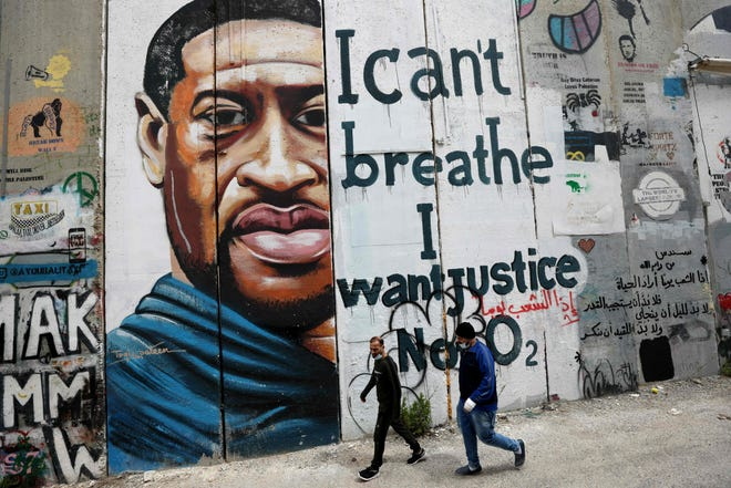 People walk past a mural showing the face of George Floyd, an unarmed handcuffed Black man who died after white police officer Derek Chauvin knelt on his neck.
