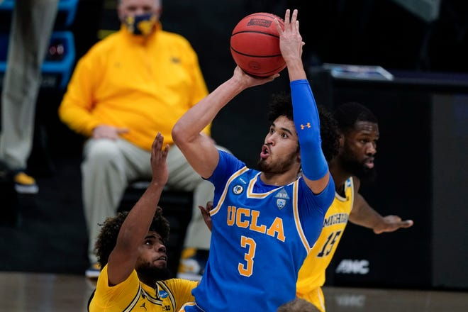 UCLA guard Johnny Juzang shoots over Michigan guard Mike Smith during the first half.