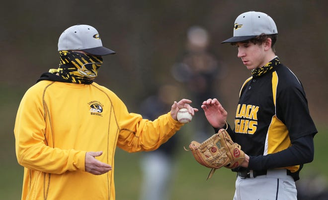 Cuyahoga Falls baseball coach Brian Shannon hands the ball off to relief pitcher Hunter Novak during the second inning of a baseball game against Archbishop Hoban, Wednesday, March 31, 2021, in Akron, Ohio. [Jeff Lange/Beacon Journal]