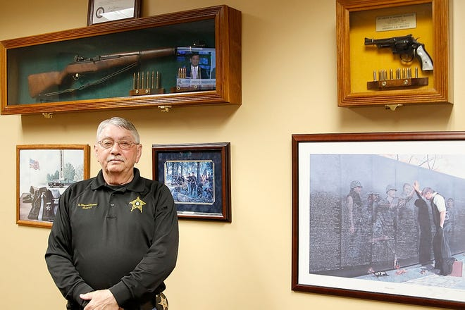 Sheriff E. Wayne Risner poses in his office on Thursday, April 1, 2021 behind him on the wall is a M1 from World War II-Korea and a 357 Smith & Wesson that was Sheriff T.R. Brown's service weapon. Risner is the 36th Sheriff in the history of Ashland County is the longest serving, now in his sixth term. TOM E. PUSKAR/TIMES-GAZETTE.COM