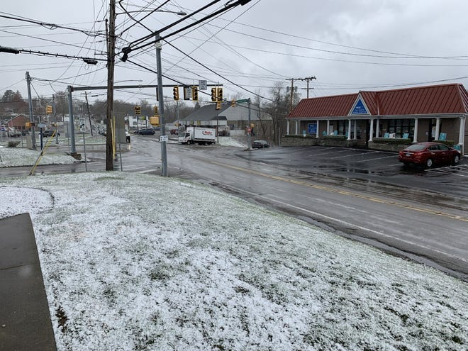 The signs of recent snowfall can be seen Thursday afternoon on the grass at Hopewell Township's Five Point intersection.