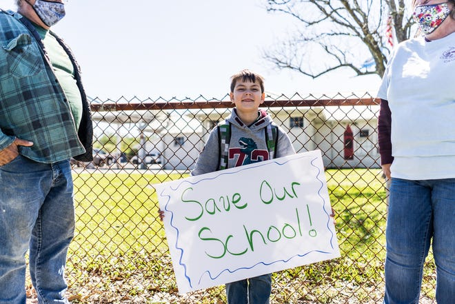 Casey Dardar, 6, a first-grader at Pointe-aux-Chenes Elementary, protests the school's closure with parents and other students April 1 outside the school.