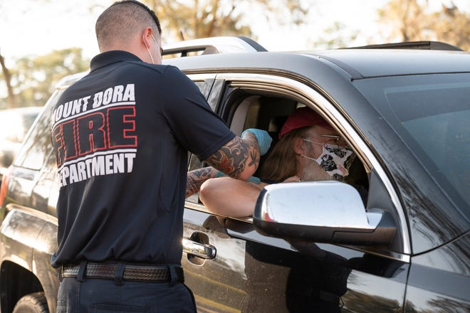 Mount Dora Firefighter and Paramedic Carlos Cervantes administers a COVID-19 vaccine to a Lake County  teacher recently in Mount Dora. [Cindy Peterson/Correspondent]
