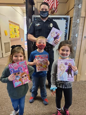 Byesville Police Department Officer Daulton Dolan stands with Byesville Elementary school students Harper Huff, Berendan Gable and Avery Cooper. The police department recently received an anonymous donation of more than100 new coloring books, which were distributed at the elementary school.