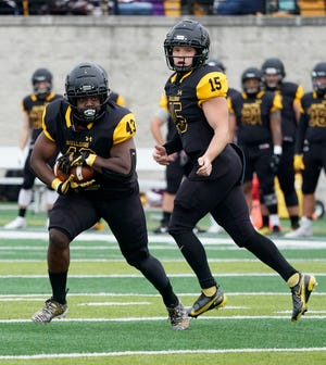 Adrian College running back Steven Moses carries the ball after Jack Wurzer hands it off during the fall game against Trine in 2020.