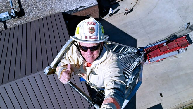 William Deal climbed the 85-foot ladder at 65 years old, reaching the top one last time before the truck is donated. His wife watched from below, and it was the first time she had seen him climb the ladder.