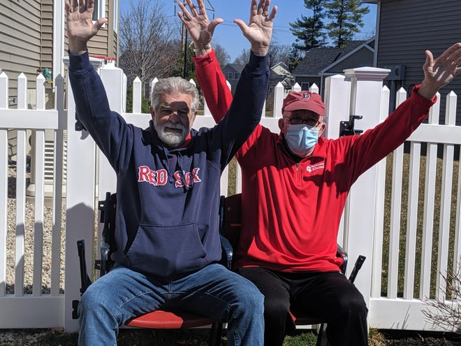 Bob Berry, left, and Ron Cole sit in real Red Sox seats to celebrate Red Sox Opening Day.