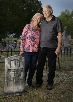 Myra and Larry Shuman, married 50 years ago at Pigeon Creek Primitive Baptist Church, stand by the headstone of Elizabeth Walker, one of the early members of the church that started 200 years ago. Myra Shuman can trace her family back to the original 12 founding members of the congregation.