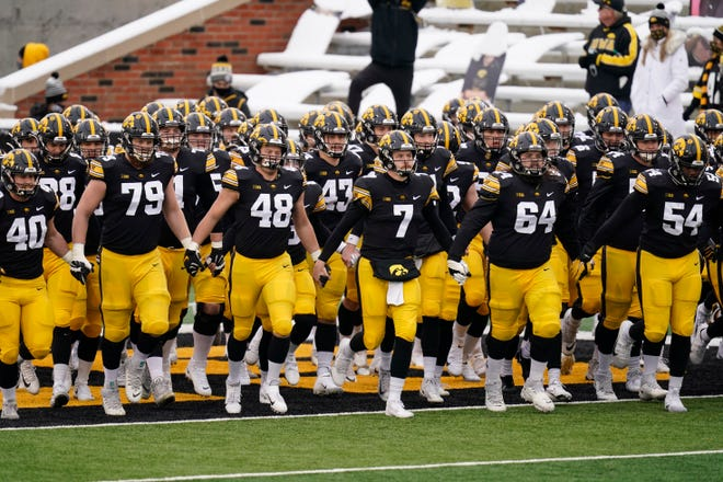 Iowa players run onto the field before a game against Wisconsin on Saturday, Dec. 12, 2020, in Iowa City, Iowa.