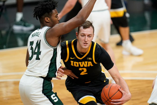 Iowa's Jack Nunge (2) drives on Michigan State forward Julius Marble II (34) in the first half of a basketball game in East Lansing, Mich. on Saturday, Feb. 13, 2021.