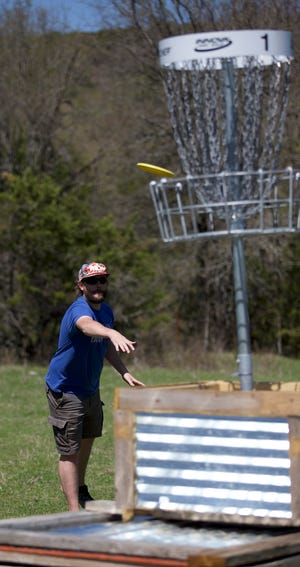 Ed Churchill, 31, from Glen Rose, finishes Hole No. 1 at Dino Hills Disc Farm on its opening day on Friday, March 23.