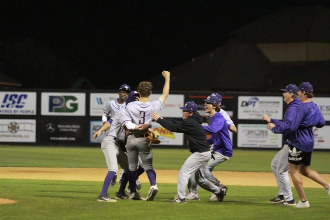 Ascension Catholic players mob pitcher Bryce Leonard after he strikes out the final Dutchtown batter in the Bulldogs' 3-2 victory.