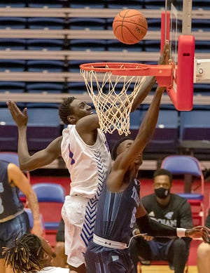 Hutchinson's Majok Kuath (1) blocks the shot of Colby's Tyrone Marshall (0) during their game Wednesday night at the Sports Arena.