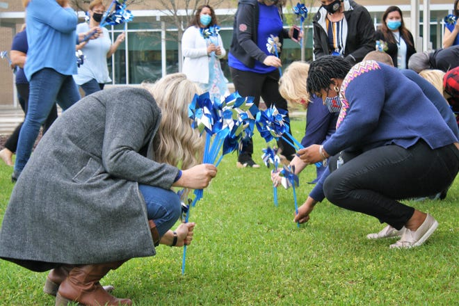 In observance of Child Abuse Prevention Month, Onslow Department of Social Services wore blue on Thursday, April 1, and gathered around the flag pole at the Consolidated Human Services Building to create a Pinwheel Garden.