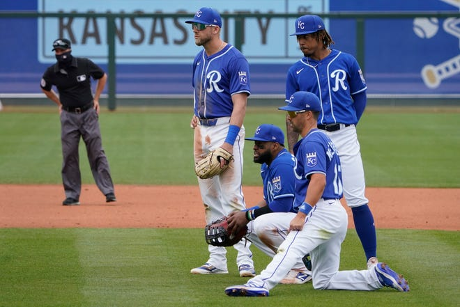 Kansas City Royals infielders, from left, Hunter Dozier, Carlos Santana, Whit Merrifield and Adalberto Mondesi watch during a pitching change in the fifth inning of a spring training baseball game against the Arizona Diamondbacks, Thursday, March 25, 2021, in Surprise, Ariz.