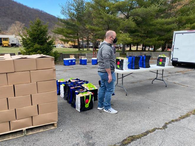 Corey Edmonds, community health worker, helps distribute food at the recent Mountain  Laurel food giveaway.